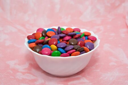 beanies: bowl of smarties on pink background Stock Photo