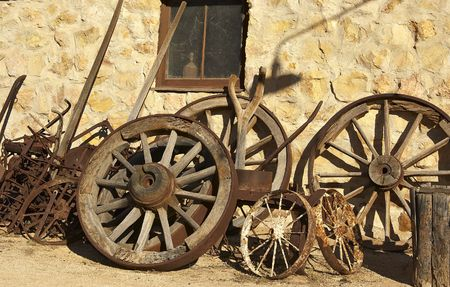 implements: pile of old cart wheels and farming implements against stone wall