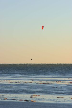 a kite surfer takes to the air above the water photo