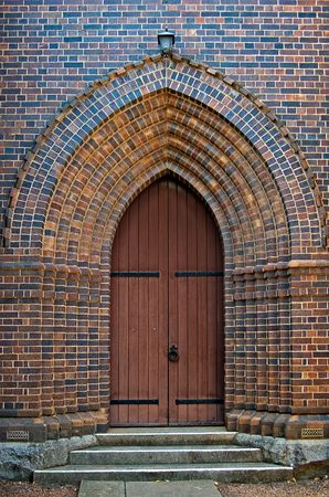 an arched brick doorway with wooden door leading into the church Stock Photo - 893811