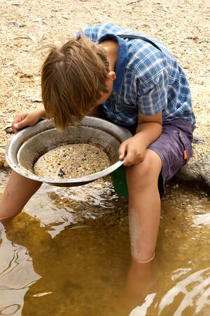 panning: a young boy looks into the pan looking for gold Stock Photo