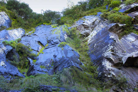 unreachable: reaching impossible heights, view looking up the blue rocks and cliff face Stock Photo