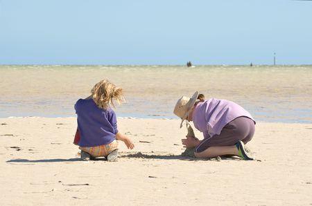 girls at the beach series: two girls sitting on the beach building sandcastles 1 of 4 in series