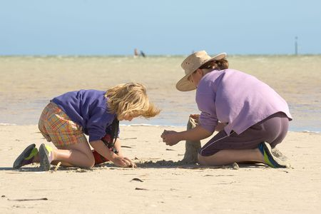 girls at the beach series: two girls sitting on the beach building sandcastles 2 of 4 in series