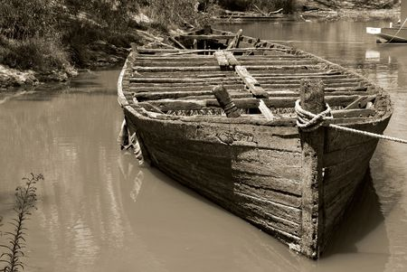 wrecked: sepia image of an old wrecked river barge hull