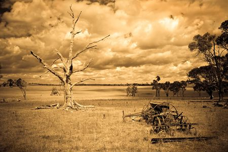 desolate: landscape of aged, sepia style image of a desolate farm with dead tree and old machinery and a storm brewing