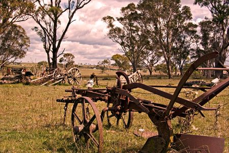 implements: an old rusting horse drawn plow sits in the farm paddock