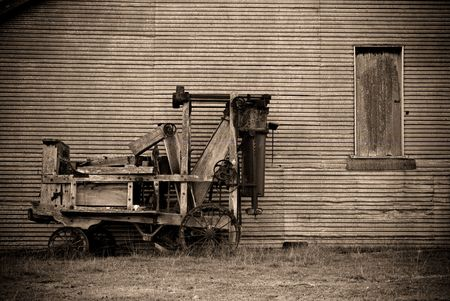 baler: an old baler in front of a barn on the farm in sepia  Stock Photo