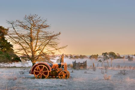 lays: an old tractor lays in the field on a cold and frosty morning