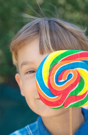 young boy looks around from behind a big swirly lollipop photo
