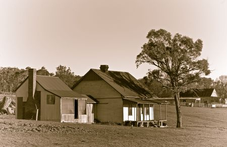 an old house of a cattle station or ranch in the middle of the field in sepia Stock Photo - 1867830