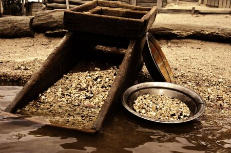 panning: old heritage gold shaker and pan in the waters edge Stock Photo