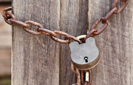 old lock and chain around wooden fence photo