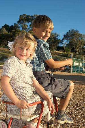 antique tricycle: young boy rides off with a girl in the back of the old tricycle Stock Photo
