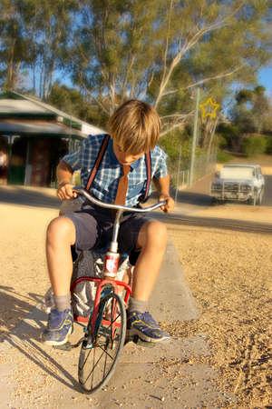 niño en paseos en ropa de estilo antiguo en un triciclo Foto de archivo - 2265990