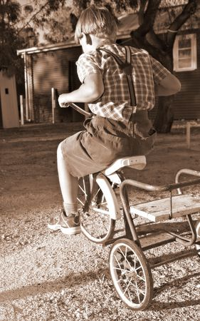 antique tricycle: young boy in old style clothing rides a tricycle Stock Photo