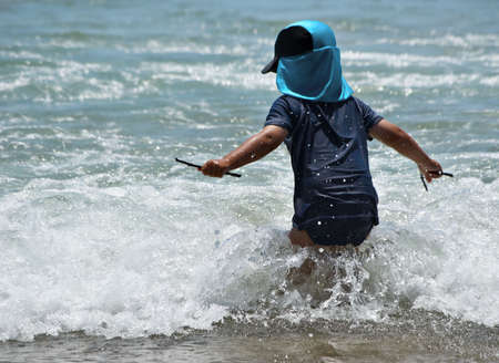 ventures: a young boy ventures into the waves at the beach Stock Photo