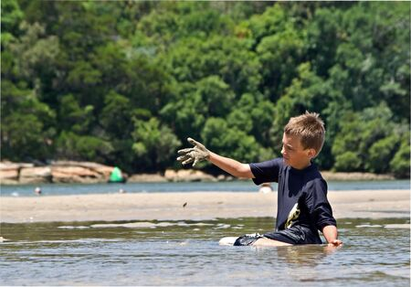 a boy sitting the water lifts a handful of mud photo
