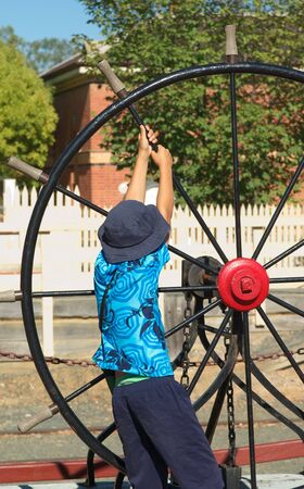 strains: young boy strains to turn an old ships wheel Stock Photo