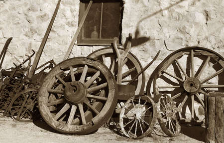 blacksmith shop: old brown image of wheels and tools outside the blacksmith shop