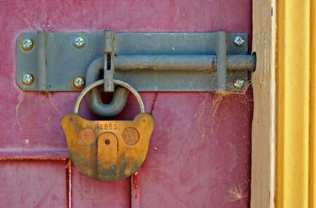 big old lock keeps this bright door shut Stock Photo - 2681006