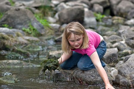 helps: young girl helps clean the weed out of the river