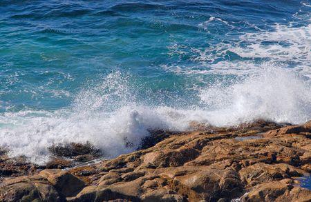 waves crashing onto this pile of rocks  photo