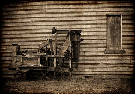 baler: grungy image of old baler in front of a barn on the farm in sepia