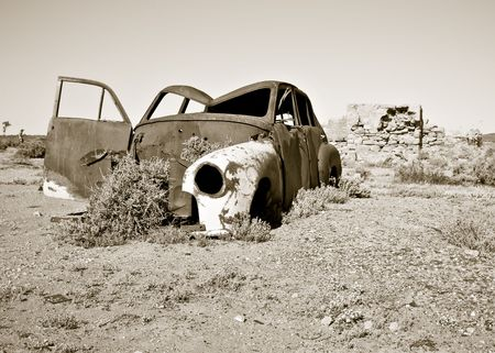 wreckage: black and white image of an old rusty car in the desert