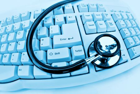 medical technology or computer problems stethoscope and keyboard on clinical blue