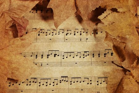 musical backgrounds: old parchment paper with music and fall or autumn leaves