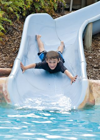 adventurous: adventurous boy comes down the slide head first
