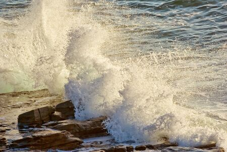 resilient: waves coming in and crashing on rocks