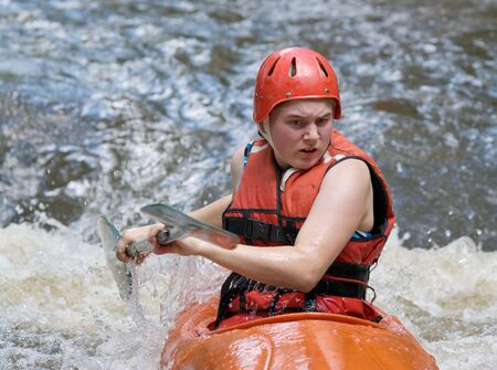 image of a teenage girl doing whitewater kayaking down a river Stock Photo - 5067023
