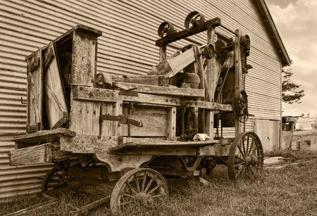 baler: an old farm machinery baler in sepia