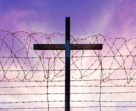 cross of christ behind rolls of barbed wire Stock Photo - 6016311