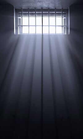 imprison: hope and despair with sun rays in this old dark prison cell Stock Photo