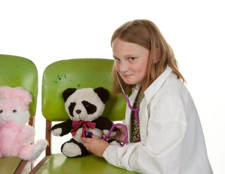 young girl playing doctor with her soft toys photo