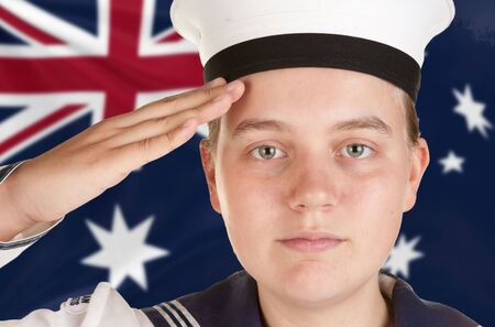 saluting: young female sailor saluting in front of australian flag