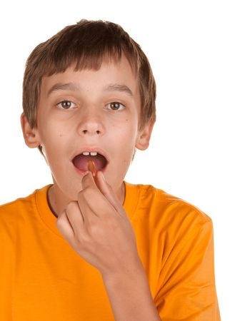 boy taking a pill isolated on white photo