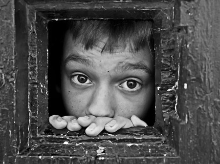 prisoner face looks out through the jail window Stock Photo - 7022735