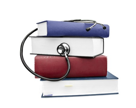 clinical research: medicine and health books with stethoscope isolated on white