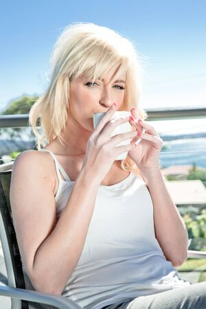 beautiful blonde woman having coffee in a restaurant photo