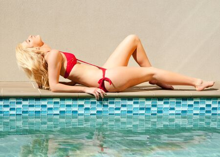 beautiful young woman in swimsuit by the swimming pool photo