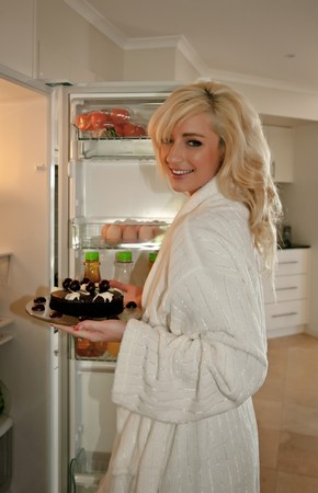 getting late: young woman getting food out of fridge for a late night snack