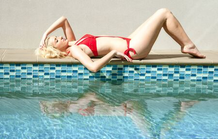 beautiful young blonde woman by the swimming  pool photo