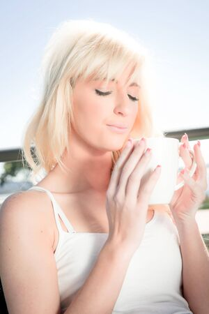 high key image of a beautiful blonde woman having coffee in a restaurant photo