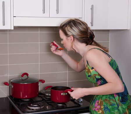 young pretty woman at the stove cooking dinner Stock Photo - 8434063