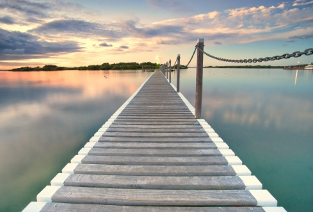 pontoon jetty across the water at sunset
