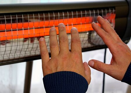 Infrared heater in the house. A man warms his hands.